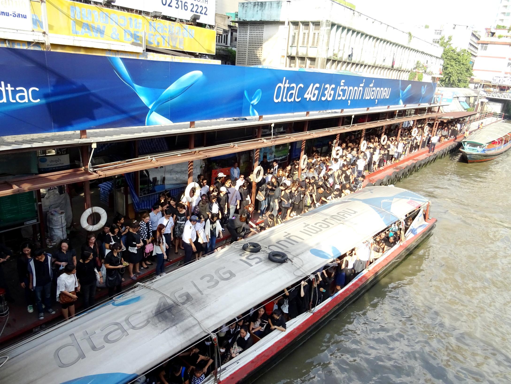 ボートで棺が王宮に移される場に向かう人々
