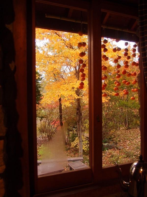 キッチンの窓越しの紅葉と干し柿