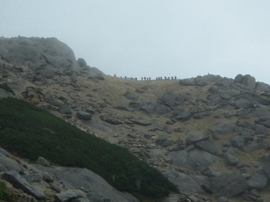 山頂直下の稜線上を行くパーティー
