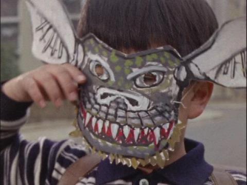 ギャンゴのお面を付けている、怪獣殿下のオサム少年