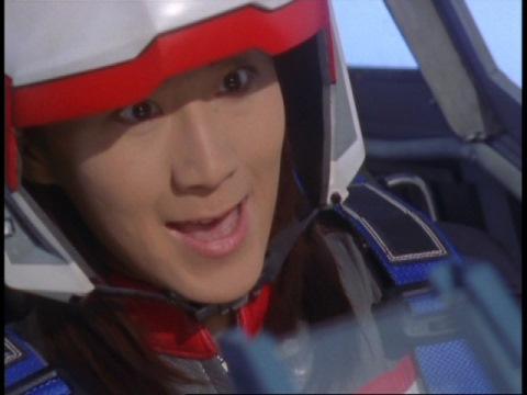 「喰らえ~!」と叫び、ギャビッシュを狙うユミムラ・リョウ隊員(演:斉藤りさ)