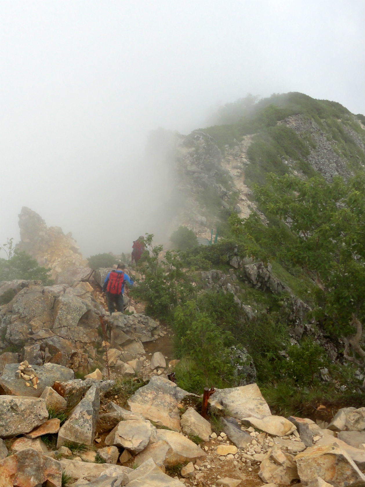 東天狗岳山頂から白砂新道に向けて下る登山者